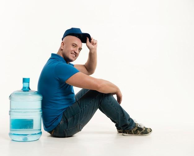水のボトルでポーズキャップを着て配達人の側面図 無料写真