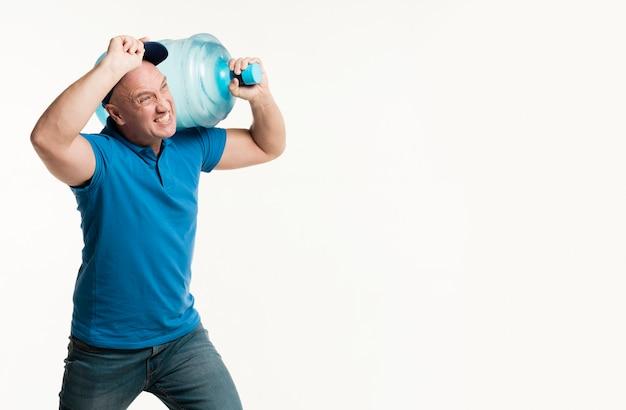 水のボトルを保持している勤勉な配達人 無料写真