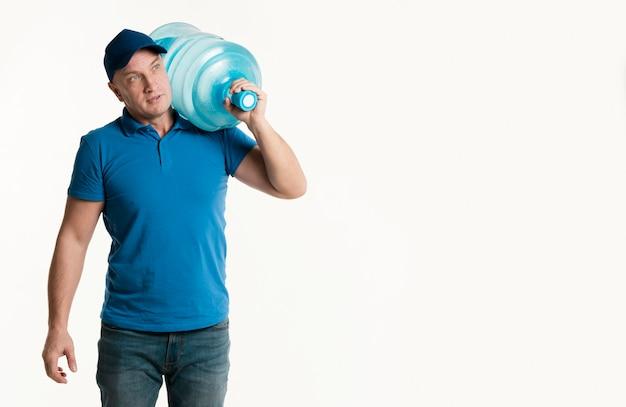 水のボトルを運んでいる間ポーズ配達人 無料写真