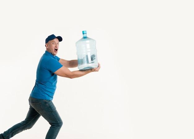 水のボトルを押しながらポーズ配達人 無料写真