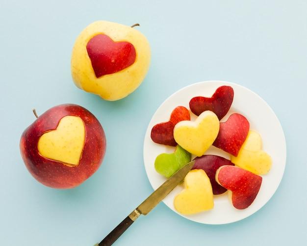 Вид сверху формы сердца фруктов на тарелку с ножом Бесплатные Фотографии
