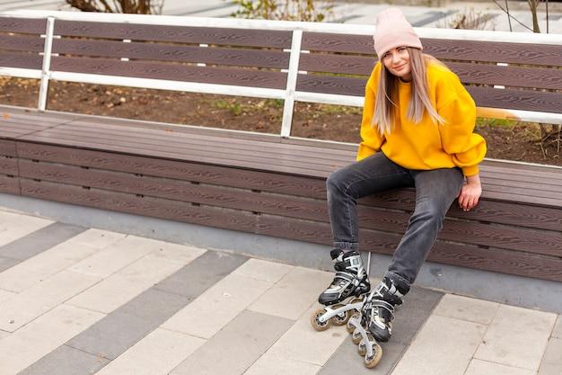 Женщина сидит на скамейке во время ношения роликовых коньков Бесплатные Фотографии
