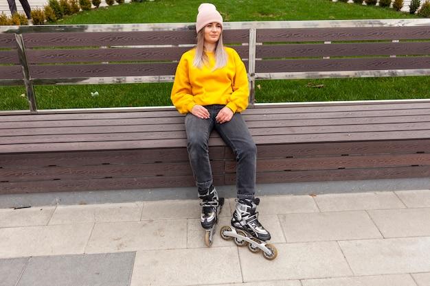 Лезвия ролика расслабленной женщины нося сидя на стенде Бесплатные Фотографии