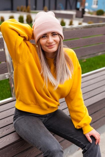 Женщина с шапочкой, улыбаясь и позирует Бесплатные Фотографии