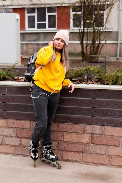 Женщина в роликовых коньках позирует с шапочкой и рюкзаком Бесплатные Фотографии