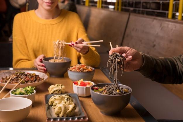 さまざまなアジア料理とテーブルの上の麺のボウル 無料写真