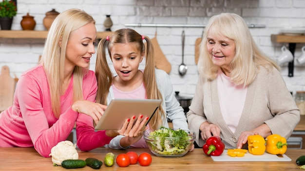 台所でタブレットを見て女性 無料写真