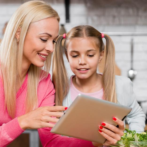 クローズアップの母と娘のデジタルタブレットを見て 無料写真