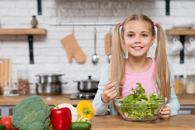 キッチンでサラダを食べるかわいい女の子 無料写真