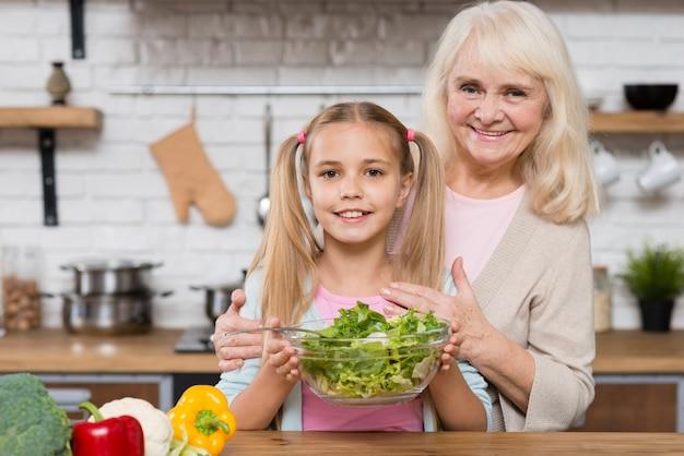 祖母と孫娘のサラダを保持 無料写真