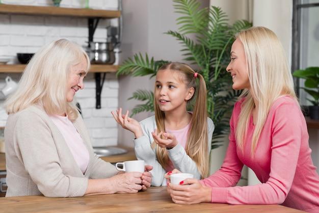 キッチンでおしゃべりする女性の世代 無料写真