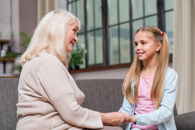 祖母と孫娘が手を繋いでいます。 無料写真