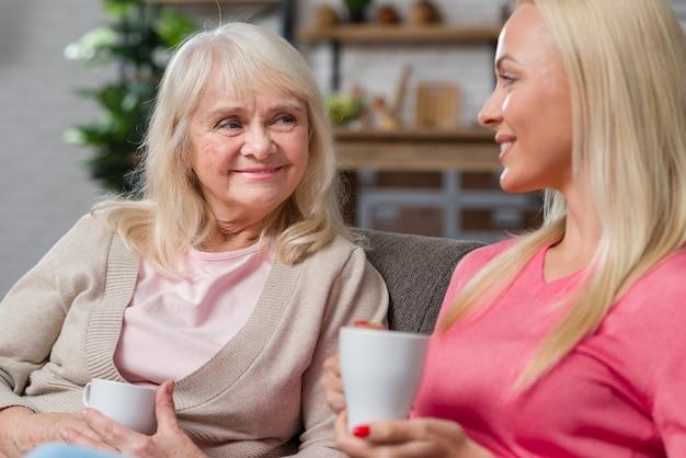 母と娘のコーヒーカップを保持しています。 無料写真