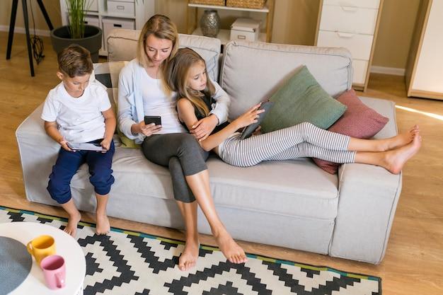 電話を見て一緒に座っている母親と子供たちのロングショット 無料写真