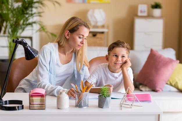 フロントビュー母と息子の宿題を屋内で 無料写真