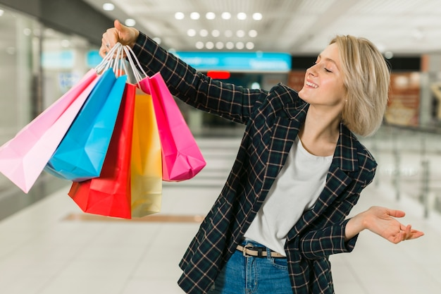 買い物袋を持って幸せな若い女 無料写真