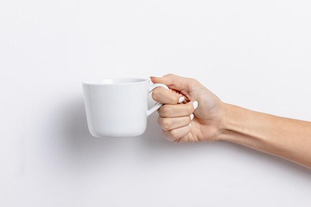 Женщина крупного плана держа белую пустую чашку Бесплатные Фотографии