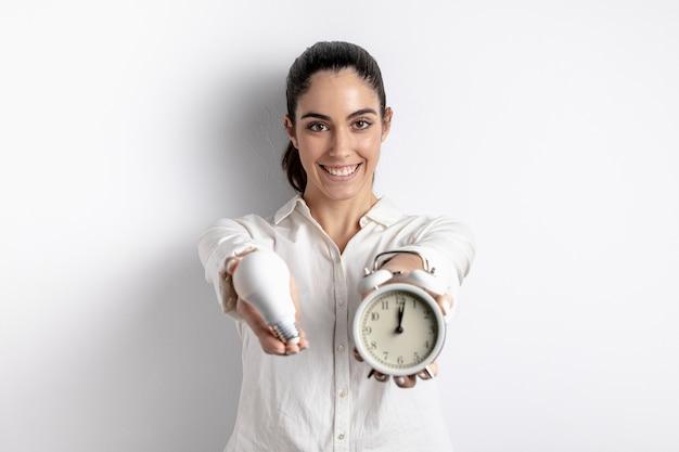 Счастливая женщина позирует с лампочки и часы Бесплатные Фотографии