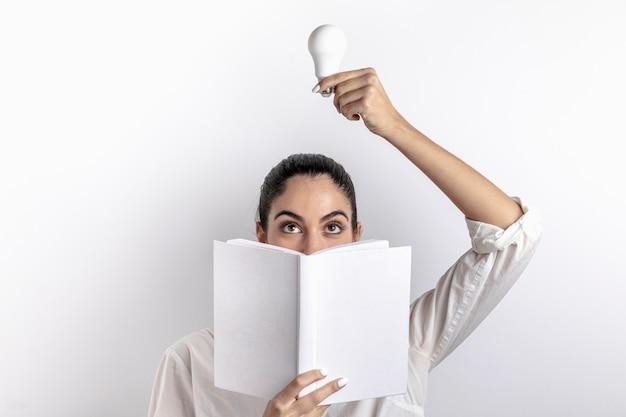 Вид спереди женщины, держащей лампочку и книгу Бесплатные Фотографии