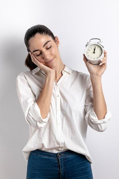 Вид спереди сонной женщины, держащей часы Бесплатные Фотографии