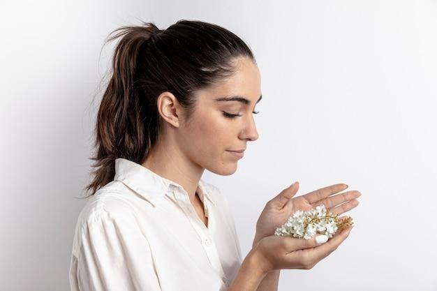Вид сбоку женщины с цветами в руках Бесплатные Фотографии