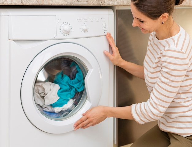 洗濯機のドアを閉める女性 無料写真