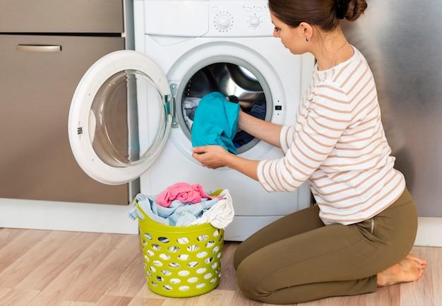 Женщина берет одежду из стиральной машины Бесплатные Фотографии