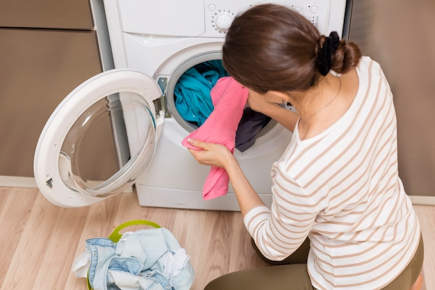 洗濯機を服を脱ぐ女性 無料写真