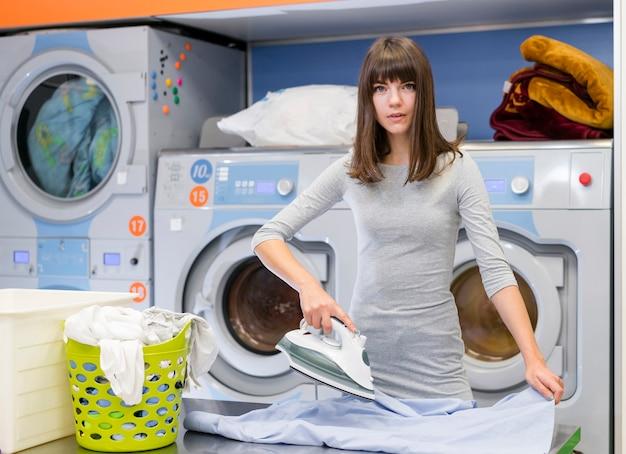 Вскользь женщина гладит одежду среднего выстрела Бесплатные Фотографии