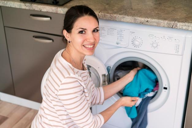 洗濯機に服を置く女性 無料写真