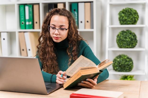 辞書とラップトップで勉強していたミディアムショットの女の子 無料写真