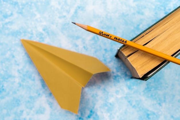 Плоская планировка с книгой, карандашом и бумажным самолетиком Бесплатные Фотографии