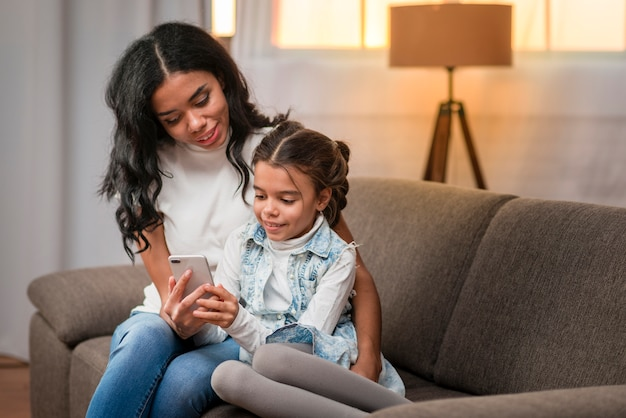 Мама учит дочь пользоваться мобильным телефоном Бесплатные Фотографии