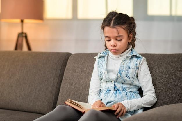 Маленькая девочка на диване рассказывает истории Бесплатные Фотографии