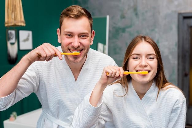 Пара позирует в халатах во время чистки зубов Бесплатные Фотографии