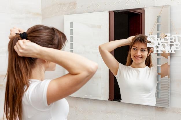 美しい女性が鏡に彼女の髪をアレンジ 無料写真