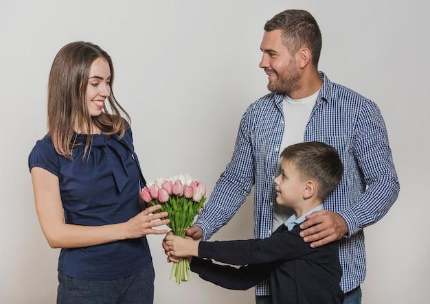 Отец и сын дарят цветы маме Бесплатные Фотографии