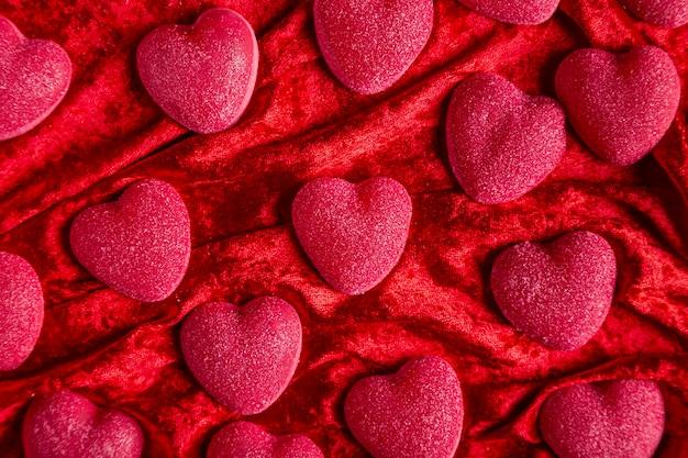 Сладкие сердечки на красной бархатной ткани Бесплатные Фотографии