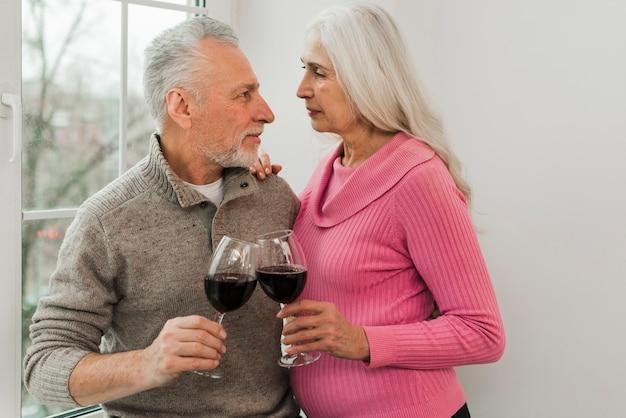 ワインのグラスを楽しむ老夫婦 無料写真