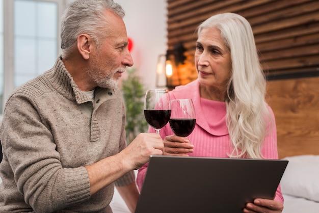 モックアップでワインを飲む年配のカップル 無料写真