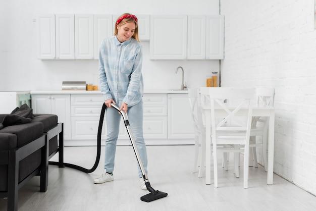 掃除機でキッチンを掃除する女性 無料写真