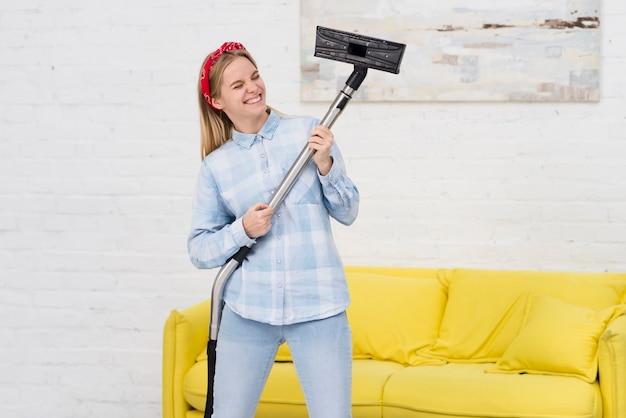 掃除と掃除機で遊ぶ女性 無料写真