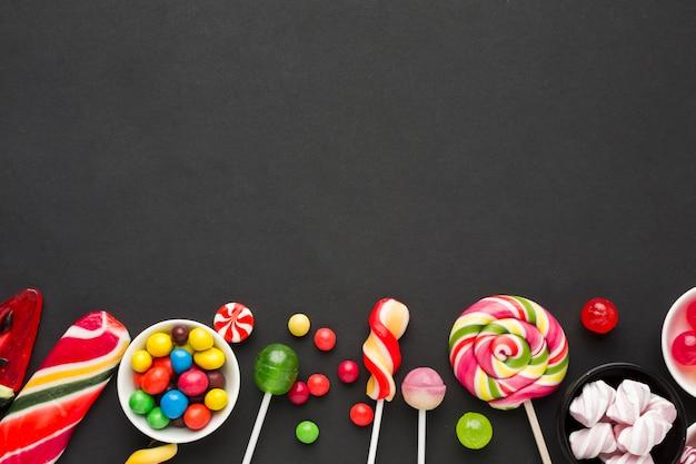 Вид сверху вкусные конфеты на черном столе Бесплатные Фотографии