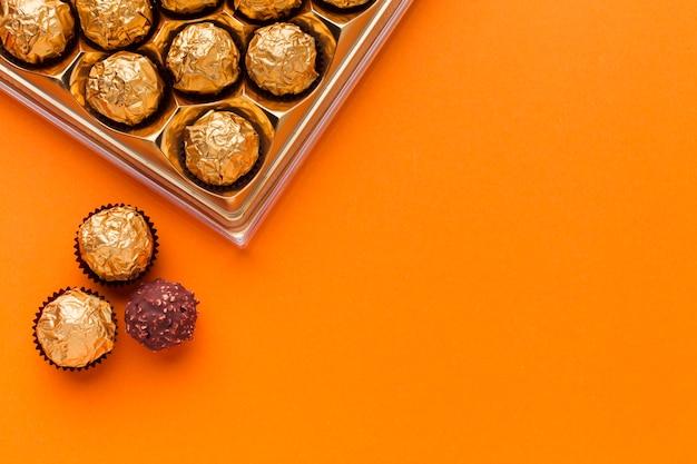 オレンジ色のテーブルにプラリネの箱 無料写真