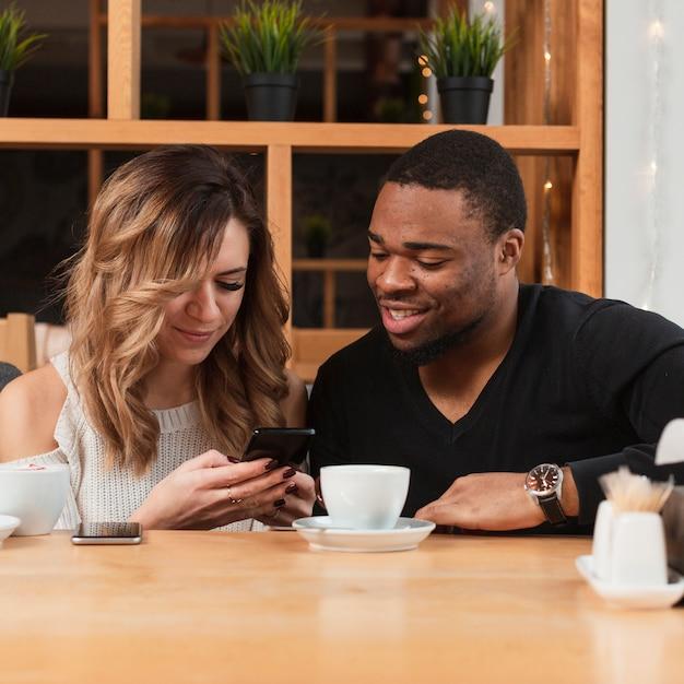 Женщина показывает мужской мобильный телефон Бесплатные Фотографии