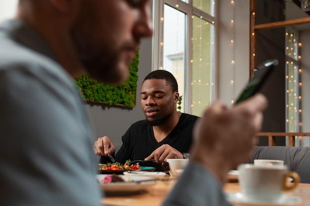 Мужские друзья в ресторане едят Бесплатные Фотографии