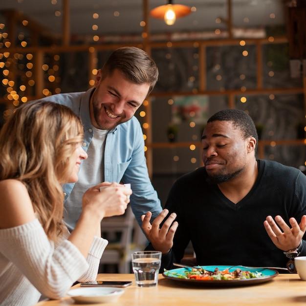 Улыбающиеся друзья в ресторане вместе Бесплатные Фотографии