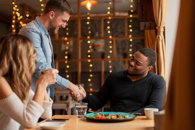 友達がレストランで握手 無料写真