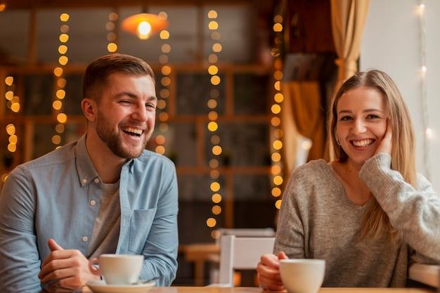 Улыбающиеся друзья в ресторане пьют кофе Бесплатные Фотографии