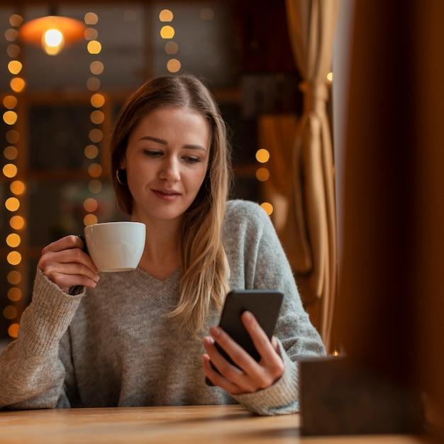 Портрет красивая женщина, глядя на телефон Бесплатные Фотографии